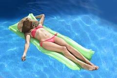 A mulher bonita no chapéu do biquini e do sol no encontro da cara relaxa no fl Fotos de Stock Royalty Free