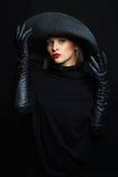 Mulher bonita no chapéu e nas luvas de couro Bruxa de Halloween Imagem de Stock Royalty Free