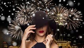 Mulher bonita no chapéu negro sobre o fogo de artifício da noite Fotografia de Stock Royalty Free