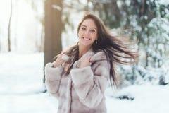 Mulher bonita no dia de inverno frio nevando na floresta Fotos de Stock Royalty Free