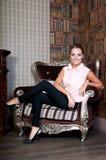 Mulher bonita no estúdio, estilo luxuoso Blusa bege Na cadeira foto de stock