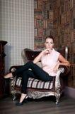 Mulher bonita no estúdio, estilo luxuoso Blusa bege Na cadeira imagem de stock