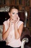 Mulher bonita no estúdio, estilo luxuoso Blusa bege Na cadeira, sorria fotos de stock royalty free