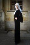 A mulher bonita no estilo gótico com cabelo louro longo perto da igreja Imagem de Stock Royalty Free