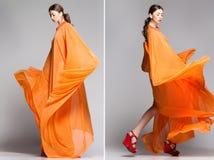 Mulher bonita no levantamento alaranjado longo do vestido dramático imagem de stock