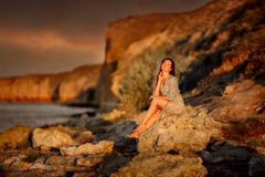 Mulher bonita no litoral das rochas no nascer do sol fotos de stock royalty free