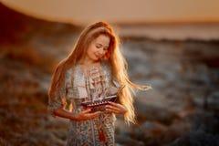 Mulher bonita no litoral das rochas no nascer do sol imagem de stock royalty free