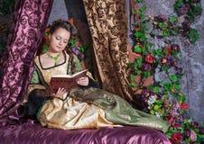 Mulher bonita no livro de leitura medieval do vestido fotos de stock royalty free