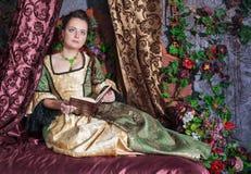 Mulher bonita no livro de leitura medieval do vestido Foto de Stock