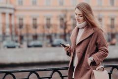 A mulher bonita no revestimento morno, guarda o telefone celular moderno, mensagens nas redes sociais, conectadas para livrar o w fotografia de stock royalty free