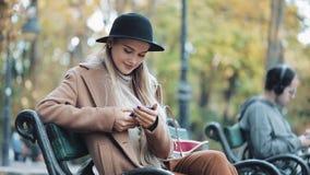 A mulher bonita no revestimento que usa o smartphone relaxa no banco no parque do outono Tecnologia fora vídeos de arquivo