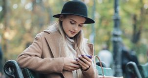 A mulher bonita no revestimento que usa o smartphone relaxa no banco no parque e no lookinginto do outono a câmera tecnologia video estoque