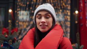 A mulher bonita no revestimento vermelho do inverno anda ao longo da rua coberta com a neve em uma cidade europeia velha bonita vídeos de arquivo