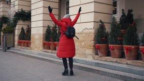 A mulher bonita no revestimento vermelho do inverno anda ao longo da rua coberta com a neve em uma cidade europeia velha bonita filme