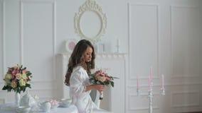 Mulher bonita no roupão que olha o ramalhete do casamento vídeos de arquivo
