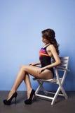 Mulher bonita no roupa de banho que senta-se na cadeira branca perto da parede azul Fotografia de Stock