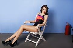 Mulher bonita no roupa de banho que senta-se na cadeira branca perto da parede azul Fotografia de Stock Royalty Free