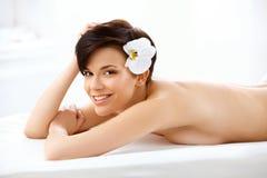 A mulher bonita no salão de beleza dos termas obtém o tratamento de relaxamento. Imagem de Stock
