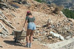 Mulher bonita no short e no tampão repicado vermelho com um carrinho de mão para o cimento