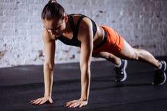 Mulher bonita no sportswear que faz a prancha quando trainnig no gym apto da cruz Foto de Stock Royalty Free