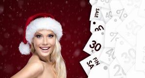 Mulher bonita no tampão do Natal com boa oferta sazonal Imagens de Stock Royalty Free