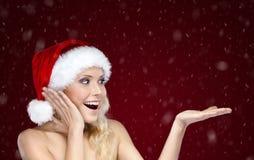A mulher bonita no tampão do Natal gesticula a palma acima fotos de stock royalty free