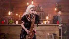 Mulher bonita no traje preto da fase que joga uma melodia no saxofone filme