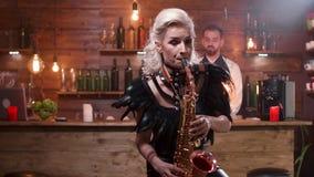 Mulher bonita no traje preto da fase que joga uma melodia no saxofone video estoque