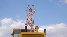 A mulher bonita no vestido aumenta os braços para o céu que está à capota da ceifeira de liga no céu azul do fundo vídeos de arquivo