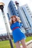 Mulher bonita no vestido azul contra a construção Imagens de Stock