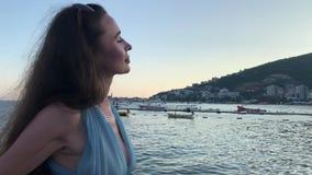 A mulher bonita no vestido azul está no beira-mar no eventing video estoque