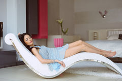 Mulher bonita no vestido azul que descansa em uma cadeira na casa Fotografia de Stock Royalty Free