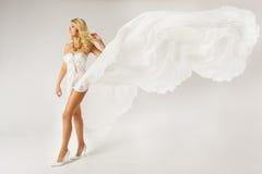 Mulher bonita no vestido branco com tela do voo foto de stock royalty free