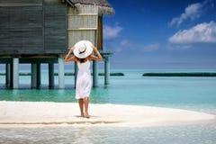 A mulher bonita no vestido branco está em uma praia em Maldivas imagens de stock royalty free