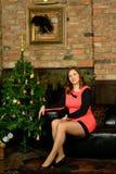 Mulher bonita no vestido de noite azul que senta-se perto da árvore de Natal Fotografia de Stock Royalty Free