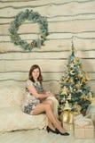 Mulher bonita no vestido de noite azul que senta-se perto da árvore de Natal Fotos de Stock
