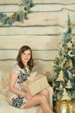 Mulher bonita no vestido de noite azul que senta-se perto da árvore de Natal Imagens de Stock