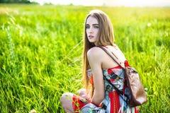 Mulher bonita no vestido e saco que senta-se na clareira Fotografia de Stock Royalty Free
