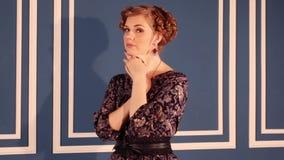 A mulher bonita no vestido levanta perto da parede na sala azul filme
