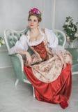 Mulher bonita no vestido medieval antiquado no sofá Fotografia de Stock