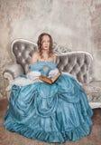Mulher bonita no vestido medieval com o livro no sofá Imagens de Stock Royalty Free