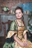 Mulher bonita no vestido medieval na cadeira Fotos de Stock Royalty Free