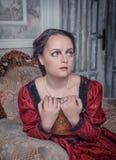 Mulher bonita no vestido medieval na poltrona Fotografia de Stock Royalty Free