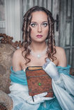 Mulher bonita no vestido medieval na poltrona Imagens de Stock