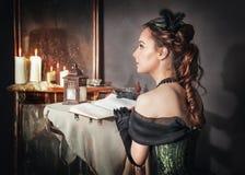 Mulher bonita no vestido medieval perto do espelho Fotografia de Stock Royalty Free