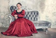 Mulher bonita no vestido medieval vermelho no sofá Fotografia de Stock Royalty Free