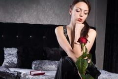 Mulher bonita no vestido preto com Rosa vermelha fotografia de stock royalty free