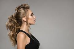 Mulher bonita no vestido preto Penteado e composição brilhante Fotografia de Stock Royalty Free