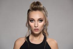Mulher bonita no vestido preto Penteado e composição brilhante Fotos de Stock Royalty Free
