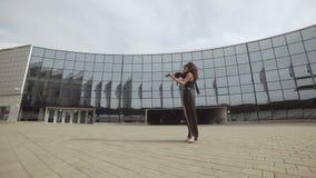 Mulher bonita no vestido preto que joga o violino perto da construção de vidro Conceito da arte video estoque